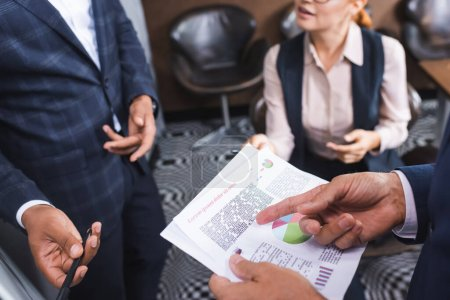 Cropped view of businessman pointing with finger at paper near blurred multicultural colleagues on background
