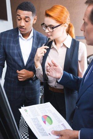 Nachdenkliche rothaarige Geschäftsfrau steht neben multikulturellen Kollegen und redet und gestikuliert im verschwommenen Vordergrund