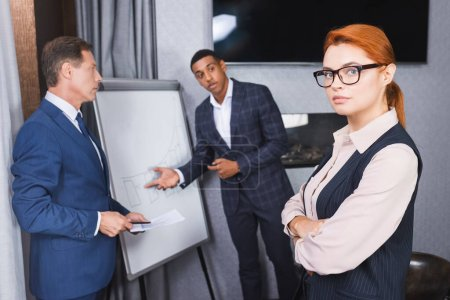 Confident redhead executive looking at camera with blurred multicultural businesspeople gesturing on background