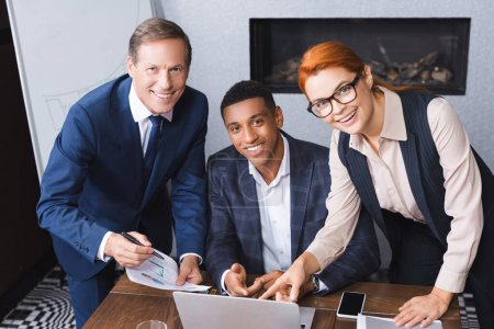 Happy multicultural businesspeople looking at camera near workplace with digital devices