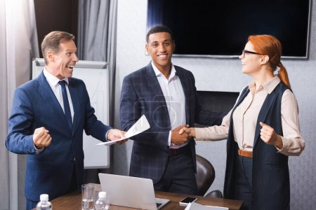 Excited businessman with yes gesture standing near multicultural colleagues shaking hands with each other in meeting room