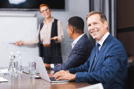 Smiling businessman looking at camera while typing on laptop with blurred multicultural colleagues on background
