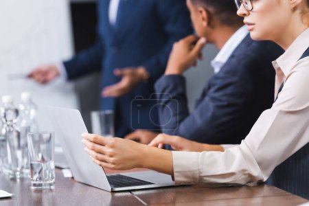 Cropped view of businesswoman using laptop while sitting at workplace with blurred multicultural colleagues on background