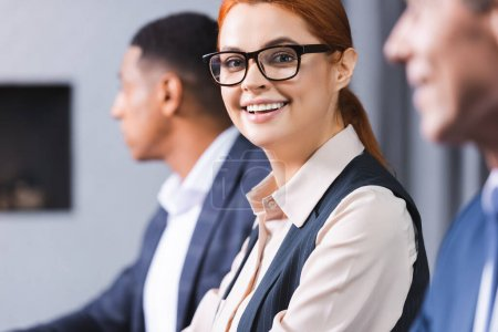 Smiling redhead businesswoman in eyeglasses looking at camera with blurred african american colleague on background