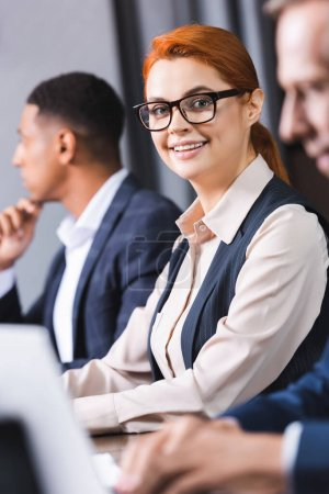 Photo for Cheerful redhead businesswoman in eyeglasses looking at camera with blurred african american colleague on background - Royalty Free Image