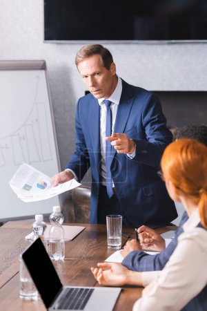 Serious executive with papers pointing with finger at businesswoman near african american colleague on blurred foreground