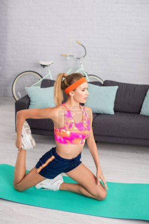 Young blonde sportswoman stretching on fitness mat at home