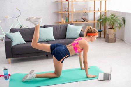Photo pour Jeune sportive blonde s'entraînant sur tapis de fitness près d'un ordinateur portable, haltères et bouteille de sport à la maison - image libre de droit