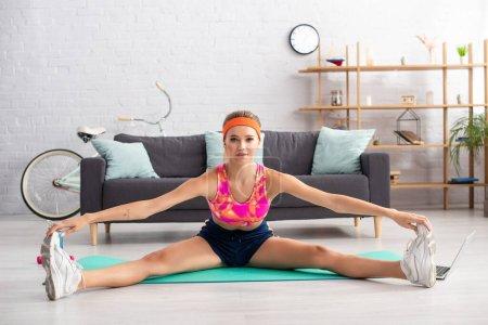 Photo pour Jeune sportive blonde regardant la caméra tout en faisant split sur tapis de fitness à la maison - image libre de droit