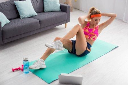 Photo pour Jeune femme blonde faisant abdos sur tapis de fitness près d'un ordinateur portable, haltères et bouteille de sport à la maison - image libre de droit