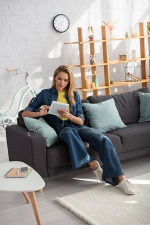 Photo for Full length of young blonde woman using digital tablet while sitting on couch at home - Royalty Free Image