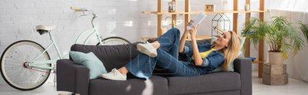 Lächelnde junge Frau beim Videoanruf auf der heimischen Couch auf digitales Tablet starrend, Banner