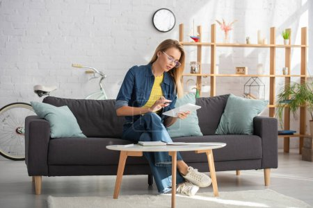 Full length of young woman using digital tablet while sitting on couch near coffee table at home