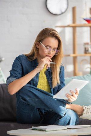 Photo pour Femme blonde réfléchie avec stylo regardant tablette numérique tout en étant assis sur le canapé sur fond flou - image libre de droit