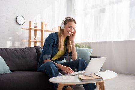 Wesoła młoda blondynka w słuchawkach patrząc na laptopa siedząc na kanapie w domu