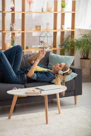 Young blonde woman in headphones texting on smartphone while lying on couch near coffee table at home