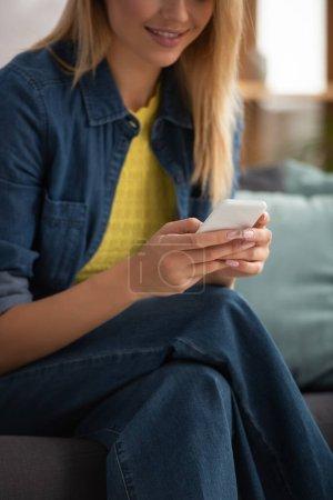 Ausgeschnittene Ansicht einer jungen Frau, die auf dem Smartphone SMS auf verschwommenem Hintergrund schreibt