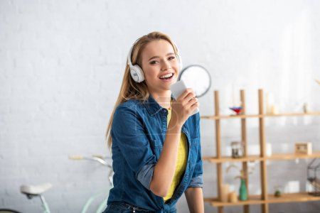 Cheerful blonde woman with smartphone looking at camera while singing at home on blurred background