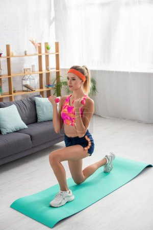 Full length of young sportswoman with dumbbells doing lunges on fitness mat at home on blurred background