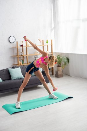 Full length of young sportswoman with outstretched hands exercising on fitness mat at home