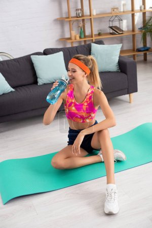 Full length of smiling sportswoman drinking water from sports bottle while sitting on fitness mat on blurred background