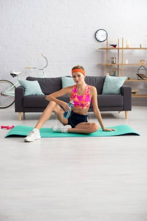 Full length of young sportswoman with sports bottle looking at camera while sitting on fitness mat at home