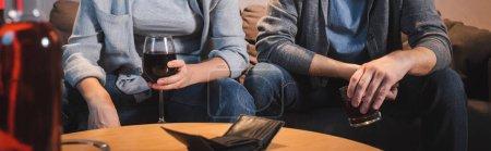 Photo pour Vue recadrée du mari et de la femme assis avec des verres d'alcool près d'un portefeuille vide, avant-plan flou, bannière - image libre de droit