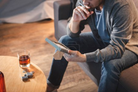 Photo for Cropped view of alcohol-addicted man holding photo frame near bottle of whiskey on table - Royalty Free Image