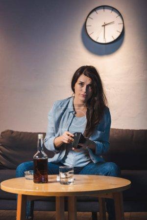 Betrunkene Frau blickt in Kamera und hält leere Geldbörse neben Whiskey-Flasche auf Tisch