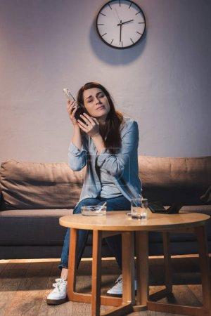 Photo pour Bouleversée, femme ivre tenant une bouteille de vin près de la tête alors qu'elle était assise seule à la maison - image libre de droit