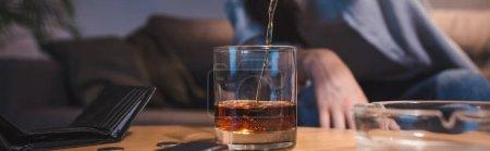 vue recadrée de la femme versant du whisky dans du verre près du portefeuille vide, bannière