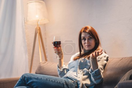 drunk, skeptical woman looking at camera while sitting with glass of red wine