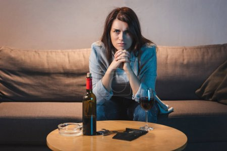 Photo for Frustrated alcoholic woman sitting at table with red wine, coins and empty wallet - Royalty Free Image