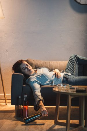 Photo for Drunk woman sleeping on sofa with glass of red wine near bottles on floor - Royalty Free Image