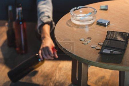 Photo pour Vue partielle de la main féminine avec bouteille d'alcool près des pièces de monnaie et portefeuille vide sur la table, fond flou - image libre de droit