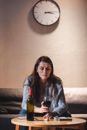 Photo pour Femme déprimée tenant un verre de vin rouge assis seul près de la bouteille et cadre photo sur la table - image libre de droit
