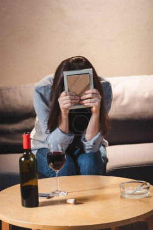 Photo for Depressed woman obscuring face with photo frame while sitting near bottle and glass of red wine on table - Royalty Free Image