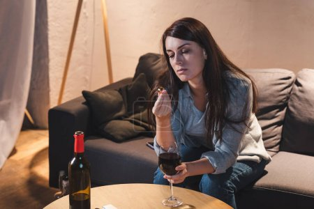 Photo for Alcohol-addicted woman holding wedding ring while sitting with glass of red wine - Royalty Free Image
