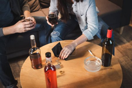 Photo pour Vue recadrée du couple tenant des verres d'alcool près des bouteilles, des pièces de monnaie et un portefeuille vide sur la table - image libre de droit