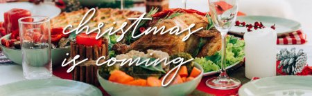 table served with delicious pie, roasted turkey and vegetables near christmas is coming lettering near candles, banner
