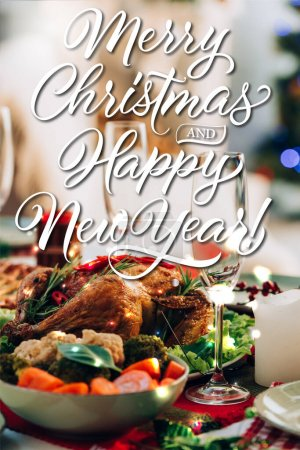 table served with delicious turkey and vegetables near merry christmas and happy new year lettering and candle