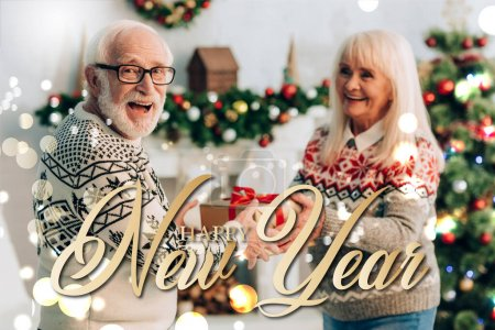 cheerful senior woman presenting gift to excited husband near happy new year lettering