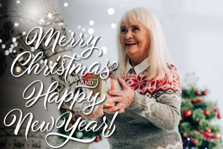 cheerful senior woman presenting gift to husband near merry christmas and happy new year lettering