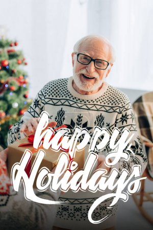 Photo for Cheerful senior man receiving christmas gift from wife near happy holidays lettering at home - Royalty Free Image