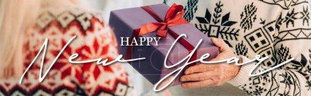 Photo pour Vue recadrée de l'homme âgé présentant cadeau de Noël à la femme près de bonne année lettrage, bannière - image libre de droit