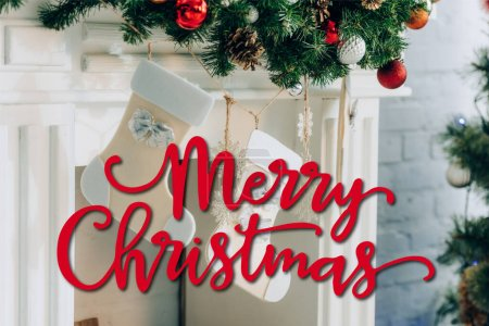 Photo for Decorated pine branch with stockings near fireplace and merry christmas lettering at home - Royalty Free Image
