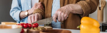 Photo for Cropped view of elderly woman near man cutting cheese on table with vegetables on blurred foreground, banner - Royalty Free Image