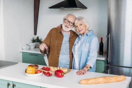 Photo pour Sourire couple âgé étreignant près de la table avec du fromage, baguette et légumes dans la cuisine - image libre de droit