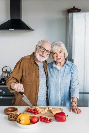 Photo pour Heureux couple âgé regardant caméra tout en étreignant près de la table avec de la nourriture dans la cuisine - image libre de droit