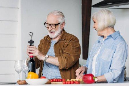 Photo pour Souriant femme âgée regardant mari ouverture bouteille de vin avec tire-bouchon dans la cuisine sur le premier plan flou - image libre de droit